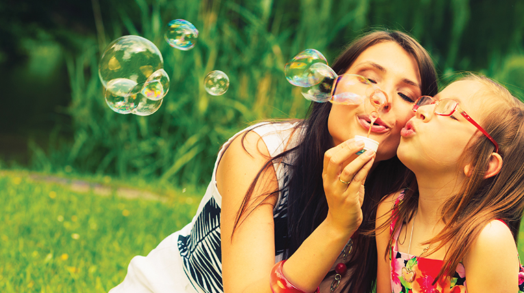 mother blowing bubbles with daughter in a park