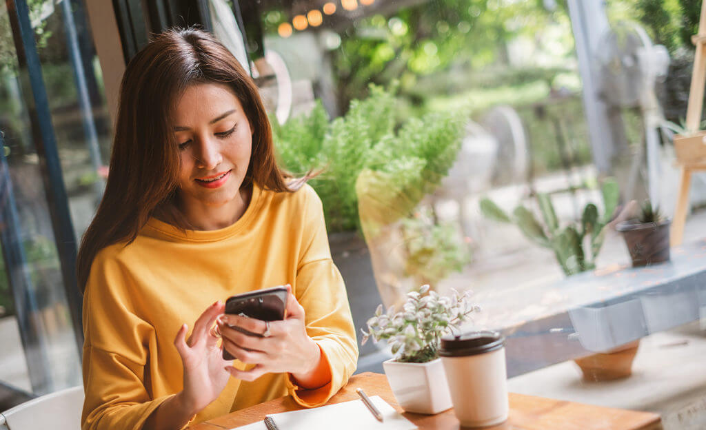 Youngwoman using smart phone for business