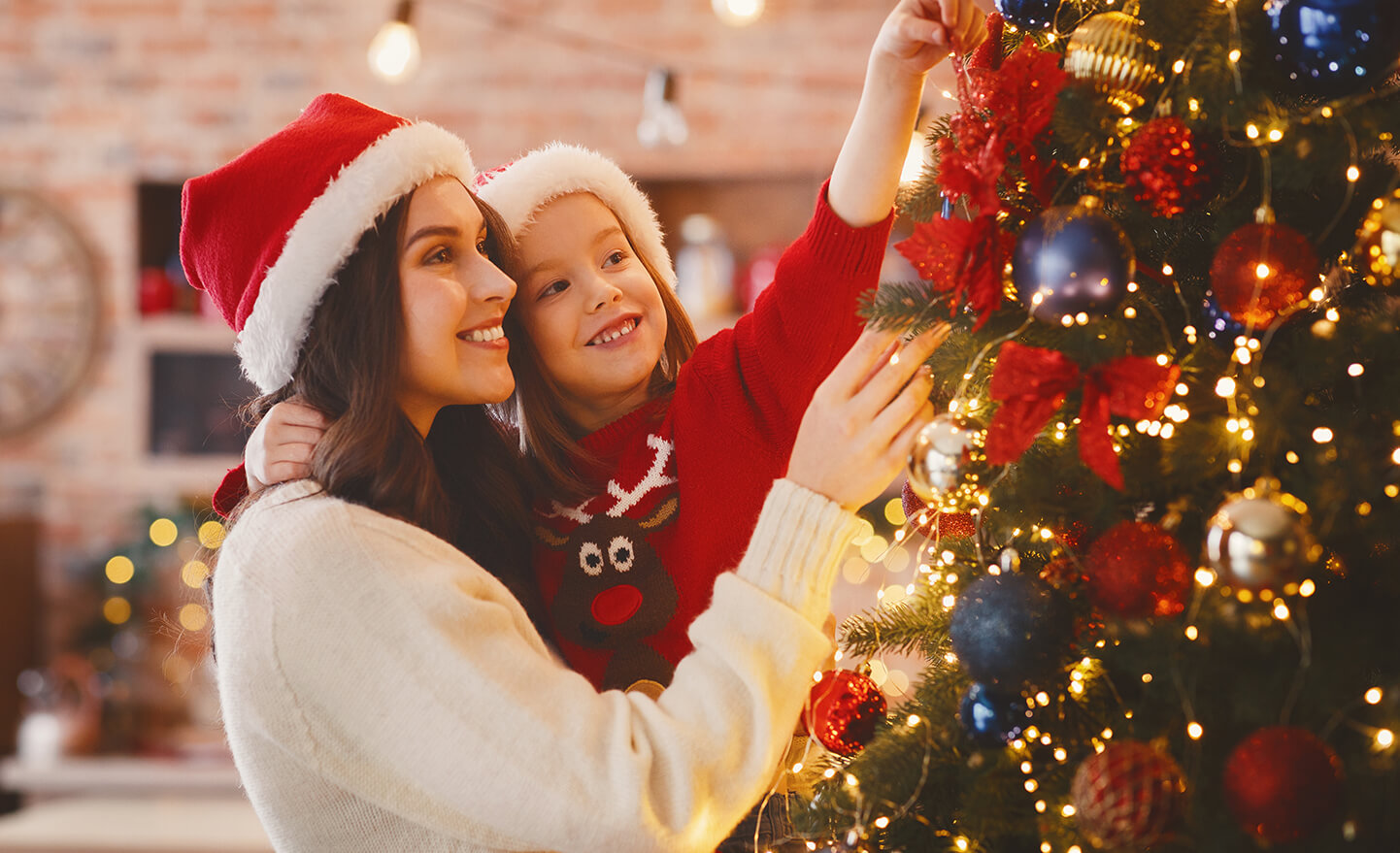 Festive mother and daughter decorating Christmas tree at home