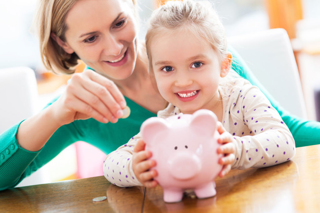 Mother teaching daughter to save money