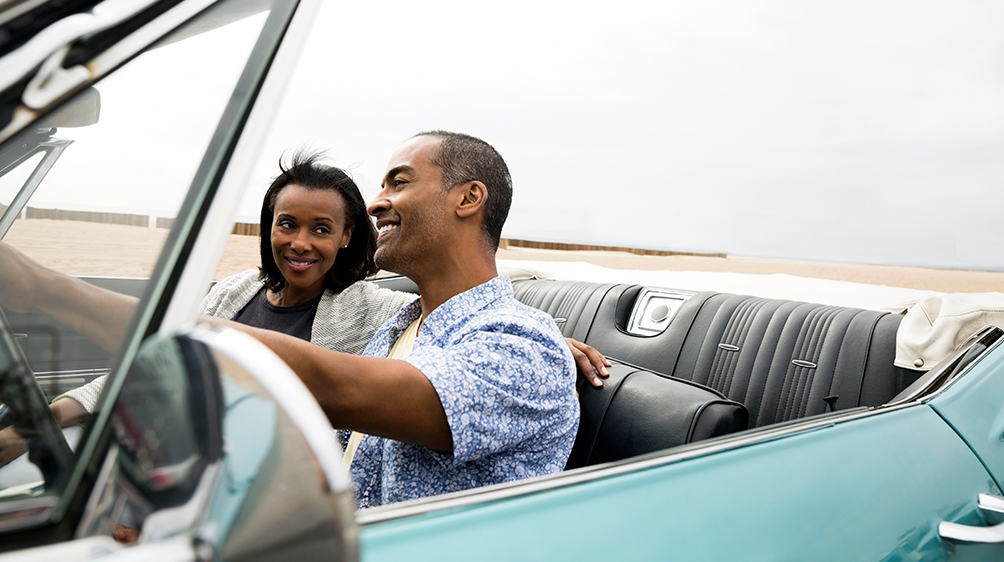 couple riding in classic car convertible