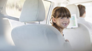 daughter-smiles-in-car-back-seat