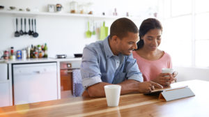 young-couple-finances-tablet-kitchen