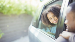 daughter smiles at dad through car window