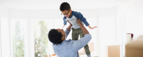 dad-lifts-young-son-up-moving-day