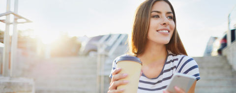 young-woman-smiling-latte-using-cell-phone