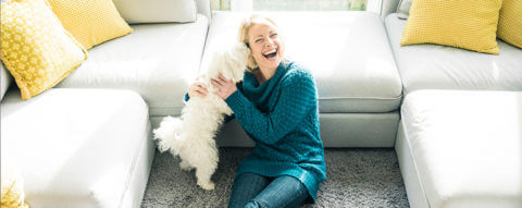 smiling-woman-wth-dog-in-living-room