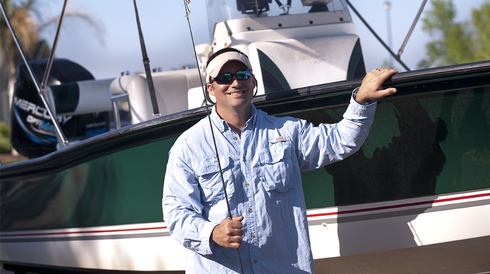 man holding fishing pole in front of new boat