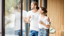 Couple looking out window while drinking coffee