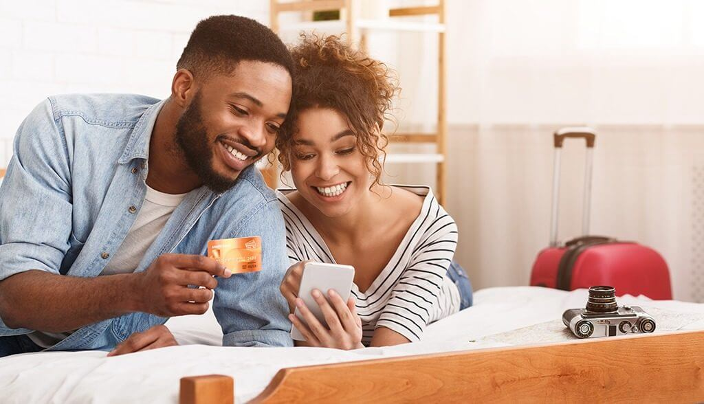 Couple laying on bed using credit card on their phone