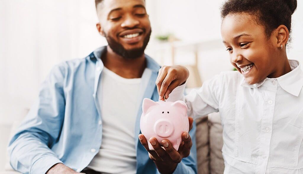 Little girl putting money in piggy jar being held by her dad