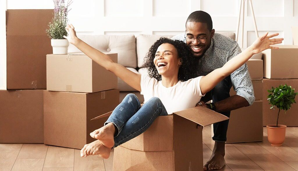 man pushing lady who is sitting in a moving box