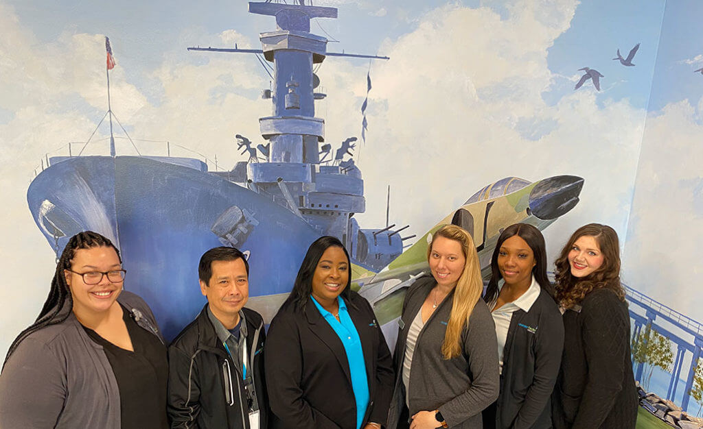 Mobile team members in front of mural of the battleship
